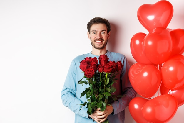 Valentines day romance. excited young man with bouquet of red roses and heart balloons smiling at camera, bring presents for lover on valentine date, standing over white background.