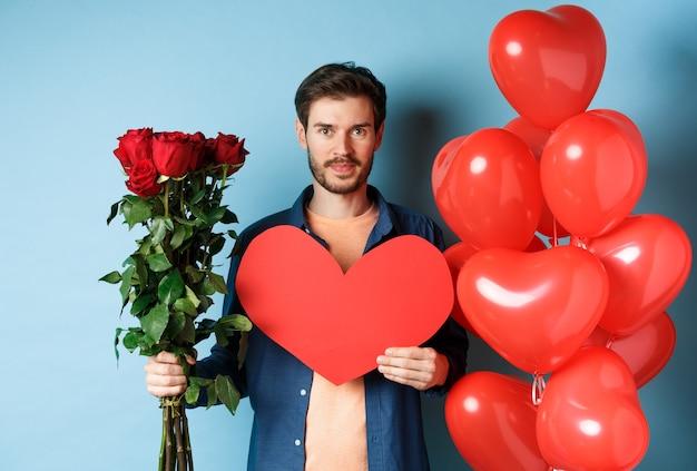 발렌타인 데이 로맨스. 빨간 장미와 하트 풍선의 부케와 젊은 남자 웃 고, 파란색 배경 위에 서있는 발렌타인 데이에 연인을위한 선물을 가져와.