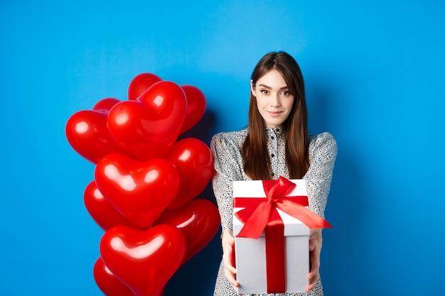 Романтичная и милая девушка на день святого валентина протягивает руки с подарком, даря подарочную коробку любовнику и ...