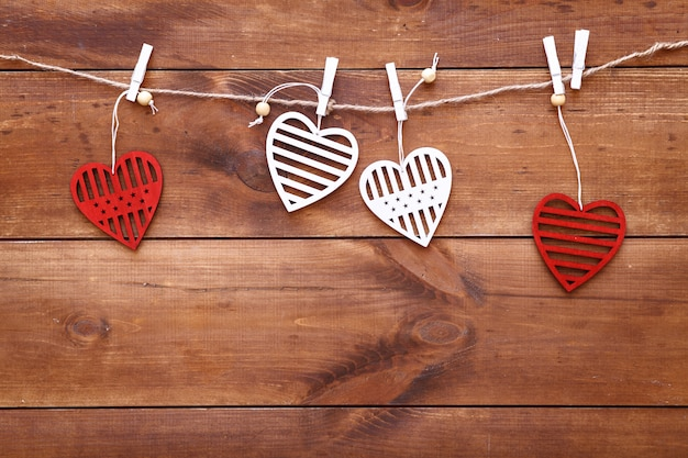 Valentines day romantic background, red and white handmade wood toy decorative hearts hanging on brown wooden table, happy holiday on february 14, dating and love concept, top view, copy free space