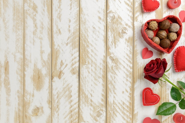 Valentines day romantic decoration with roses and chocolate on a white wooden table. top view, copy space.