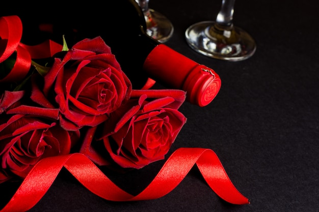 Valentines day romantic decoration with roses and red wine on a black background