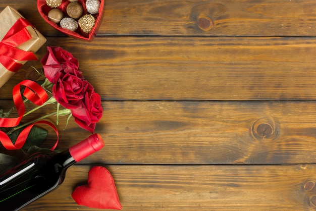 Valentines day romantic decoration with roses, wine and chocolate on a brown wooden table