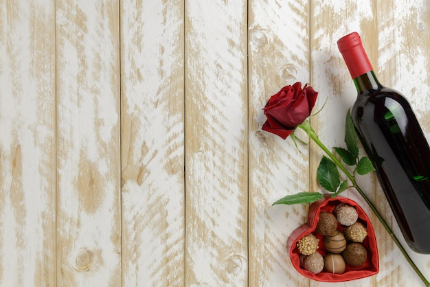 Valentines day romantic decoration with roses, wine and chocolate on a white wooden table background