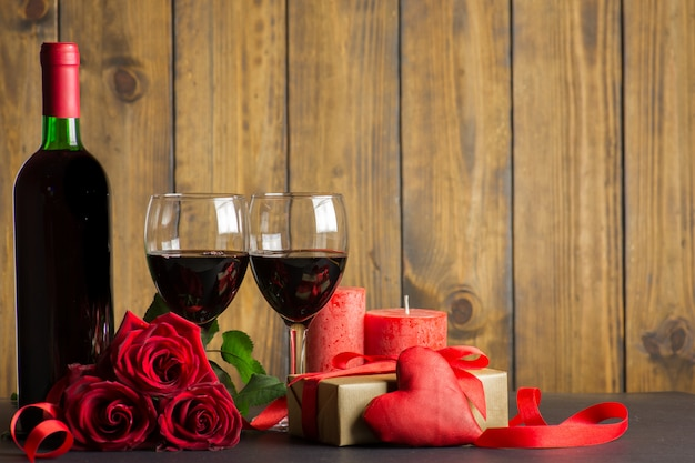 Valentines day romantic decoration with roses, wine and gift box on a brown wooden table