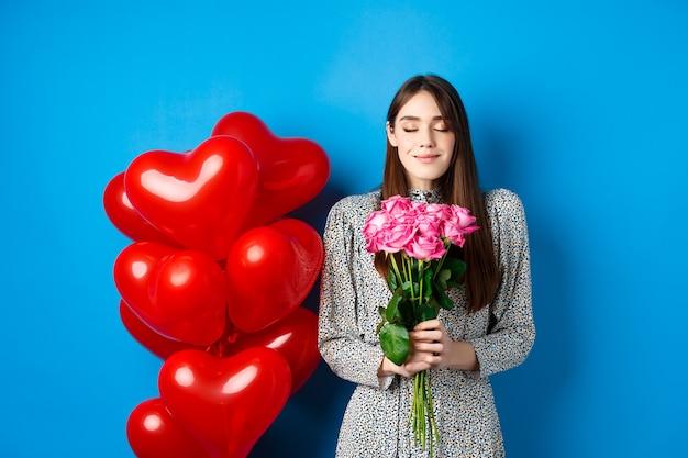 San valentino. una bella donna romantica chiude gli occhi e odora bellissimi fiori, in piedi vicino a palloncini a cuore, sfondo blu