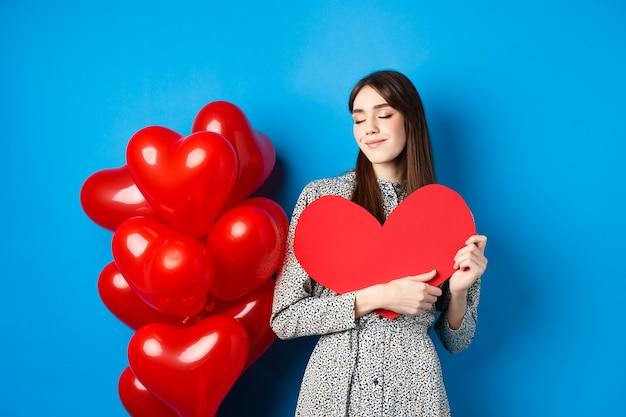 День святого валентина. романтичная улыбающаяся женщина обнимает большой красный вырез сердца и мечтает о любви, стоя в платье на синем фоне.