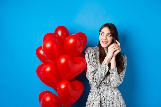 バレンタイン・デー。ドレスを着て、夢のような左を見て、笑顔、赤いハートの風船、青い背景の近くに立っているロマンチックな若い女性