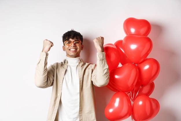 San valentino. giovane soddisfatto che dice sì, trionfa e festeggia alla data degli innamorati, fa pompa a pugno e sorride soddisfatto, in piedi vicino a palloncini a cuore su sfondo bianco.