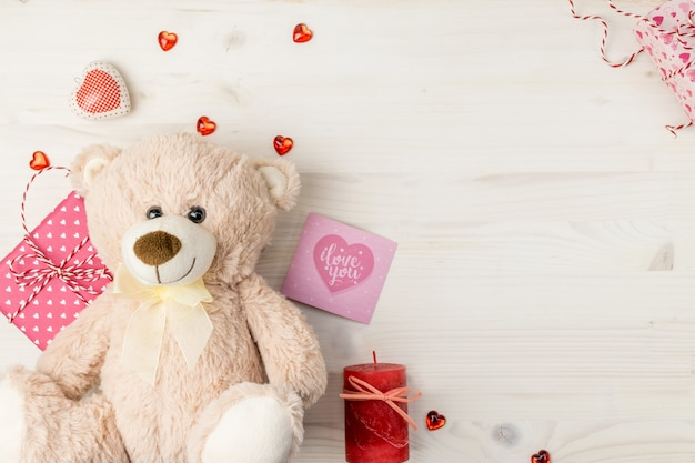 Valentines day scene with teddy bear, gift boxes, greeting card and hearts on a light wooden background.