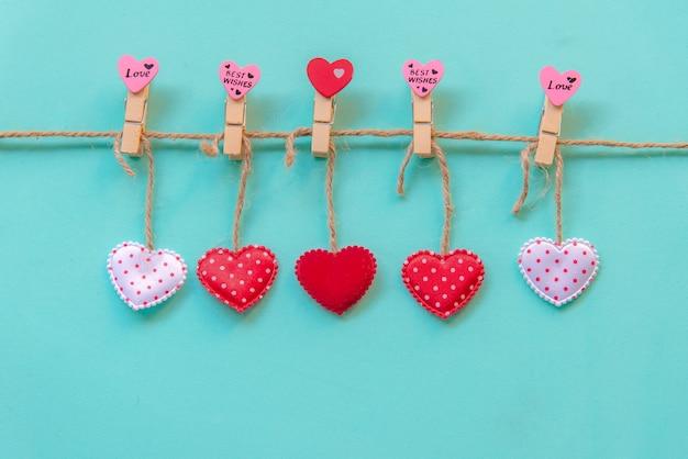 バレンタイン・デー。素朴な青いパステルカラーの壁に赤、ピンク、白の洗濯はさみに枕の心の罫線を縫い付けました。幸せな恋人たちの日カードモックアップ、コピースペース。バレンタインコンセプト