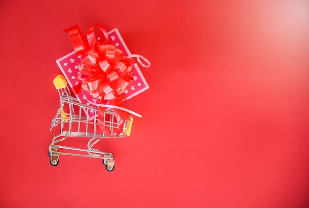Valentines day shopping and gift box pink present box with red ribbon bow on shopping cart concept merry christmas holiday happy new year