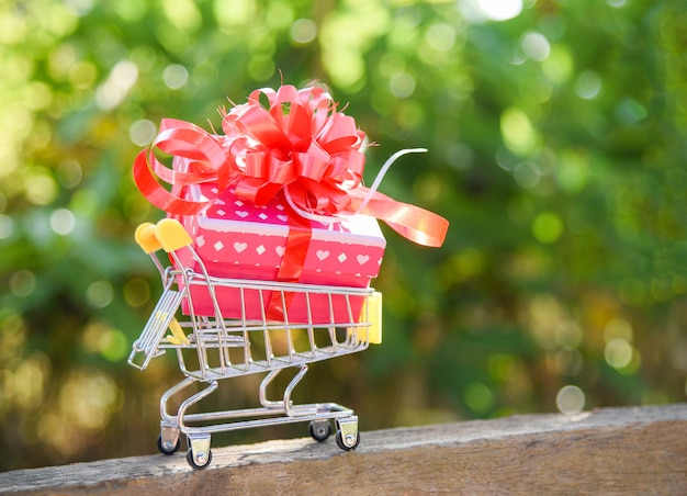 Valentines day shopping and gift box present box with red ribbon bow on shopping cart online shopping vacation