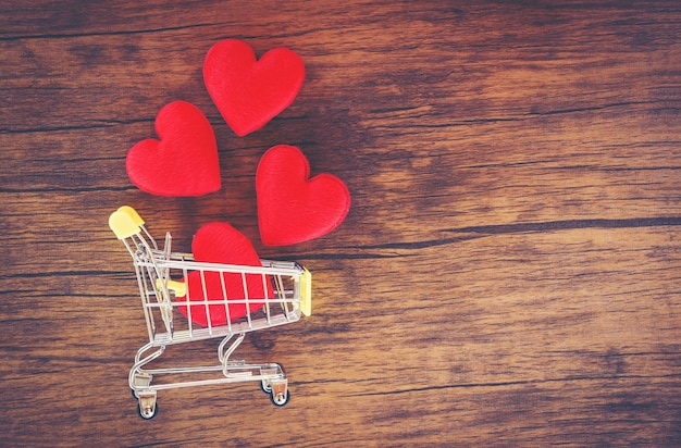 Valentines day shopping and red heart on shopping cart love shopping holiday for love valentines day on wooden background