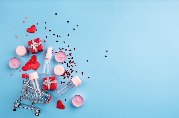 Valentines day shopping. shopping basket with various cosmetics, price tag, confetti top view flat lay on blue background