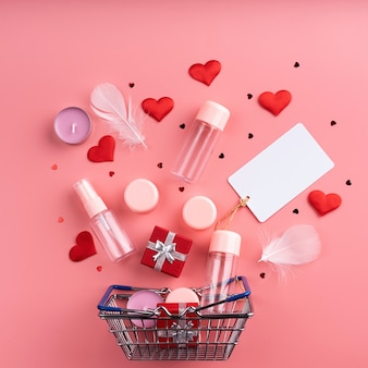 Valentines day shopping. shopping basket with various cosmetics, price tag, confetti top view flat lay on pink background