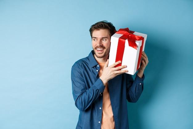 バレンタイン・デー。ギフトボックスの中身を推測している笑顔の男は、青い背景に立って、恋人のガールフレンドからプレゼントをもらいました。コピースペース