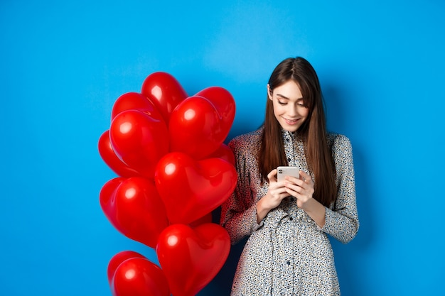 Valentines day. smiling woman in dress standing near red hearts balloons and looking at smartphone, standing on blue background.