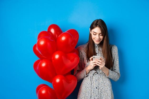 バレンタイン・デー。赤いハートの風船の近くに立って、スマートフォンを見て、青い背景の上に立っているドレスを着た笑顔の女性。
