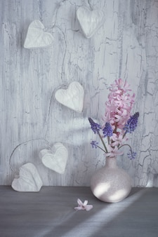 Valentines day or springtime celebration, vase with hyacinth flowers and garland lights in shape of paper hearts on rustic wood