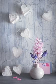 Valentines day or springtime celebration, vase with hyacinth flowers and garland lights with paper hearts