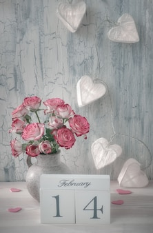 Valentines day or springtime still life, vase with roses and garland lights with paper hearts