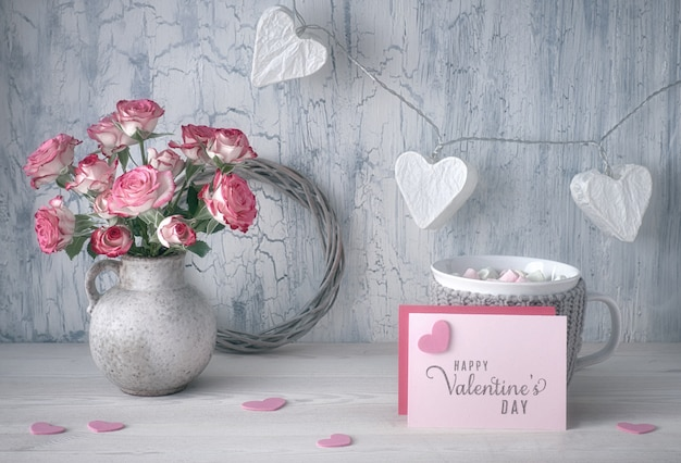 Valentines day still life, vase with roses and garland lights with paper hearts