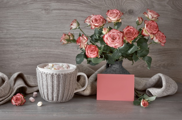 Valentines day still life with cup of hot chocolate with marshmallows, pink roses and greeting card with text