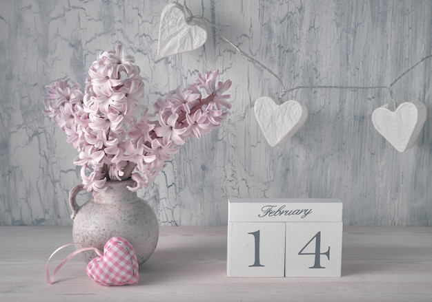Valentines day still life with wooden calendar, pink hyacinth flowers and garland lights in shape of paper hearts