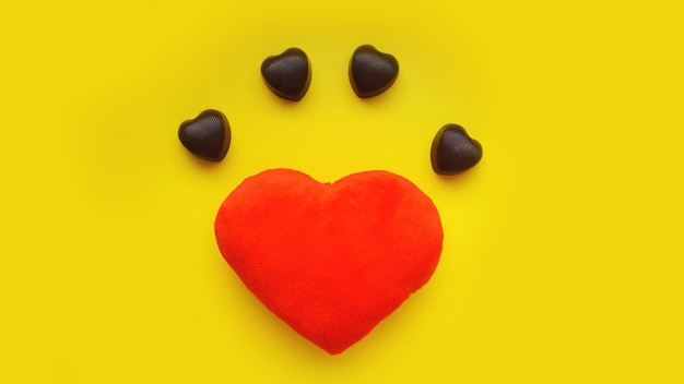 Valentines day surface with soft toy heart and chocolates on yellow surface. top view. for banner, cards design