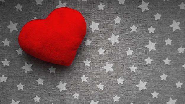 Valentines day surface with soft toy heart on a gray surface with white stars. top view. for banner, cards design