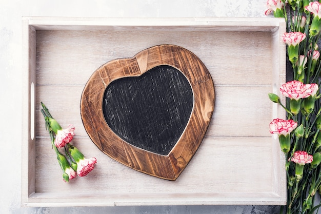 Valentines day surface with vintage slate chalk board in heart form and pink carnation flowers with copy space for text. view from above
