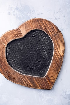Valentines day surface with vintage slate chalk board in heart form with copy space for text. view from above