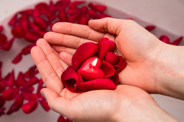 Valentines day surprise, close up woman holding red rose petals and hear candle in hands