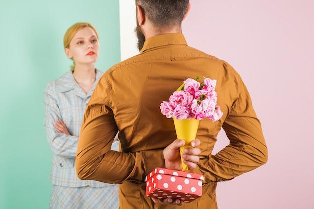 발렌타인 데이. 소녀를위한 서프라이즈. 뒤에 꽃과 선물을 숨기는 남자.