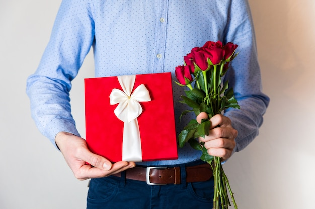 Valentines day surprise, love, handsome man holding romantic gift and red roses bouquet.