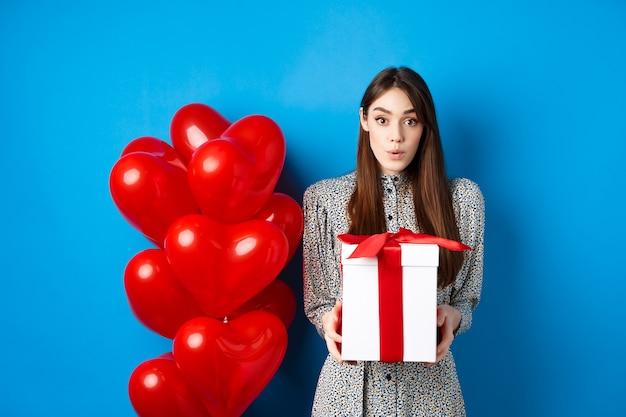 Il giorno di san valentino ha sorpreso una ragazza attraente che guarda stupita la telecamera con un grande regalo romantico in piedi...