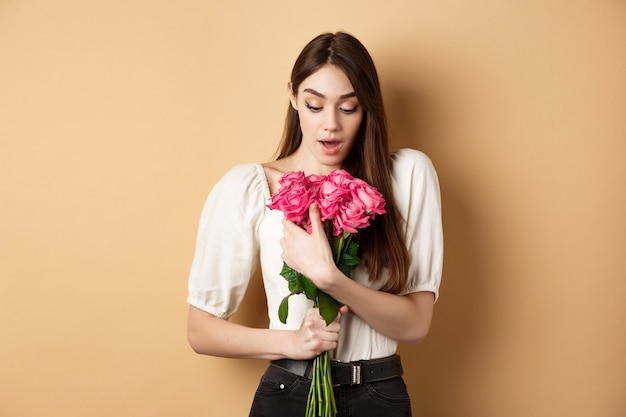 Valentines day. surprised girl receive gift from lover on date, looking amazed at beautiful bouquet of flowers, holding roses on beige background.