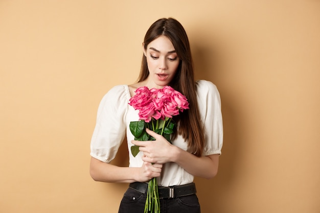 美しいピンクのバラを見ているバレンタインデーの驚いた優しい女の子は、愛からロマンチックな贈り物を受け取ります...