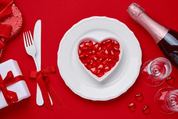 Стол или концепция дня святого валентина с пустой белой тарелкой и вилкой и ножом для столовых приборов, шампанским, очками и подарочной коробкой на алом или красном столе. плоский вид сверху с копией пространства.