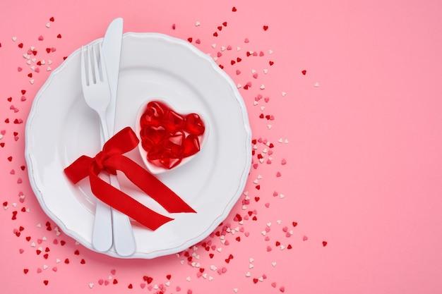 Таблица или концепция дня святого валентина с пустой белой тарелкой и вилкой и ножом столовых приборов с красной лентой на розовом столе. концепция или вид сверху плоская планировка с копией пространства.