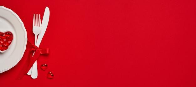 Стол или концепция дня святого валентина с пустой белой тарелкой, маленькой тарелкой в форме сердца с маленькими сердечками внутри и белыми изделиями на алом или красном столе. . вид сверху с копией пространства.