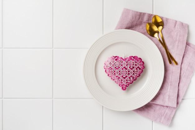 バレンタインデーのテーブルセッティング。空の白い皿、2つの金のスプーン、ピンクのリネンナプキン、白い無地のコンクリートの壁にピンクのハート。上面図とコピースペースのあるフラットレイ。