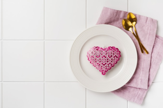 Valentines day table setting. empty white plate, two golden spoons, pink linen napkin and pink heart on white plain concrete wall. top view and flat lay with copy space.
