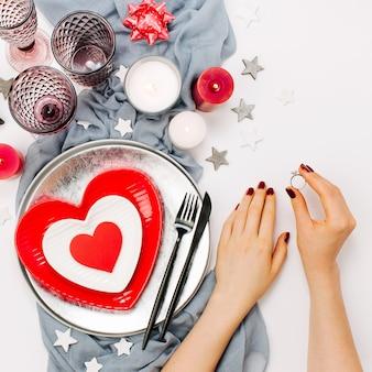 Сервировка стола дня святого валентина. женские руки держат обручальное кольцо. белые и красные блюда в форме сердца, стаканы для напитков, свечи и столовые приборы на белом фоне. романтическая концепция