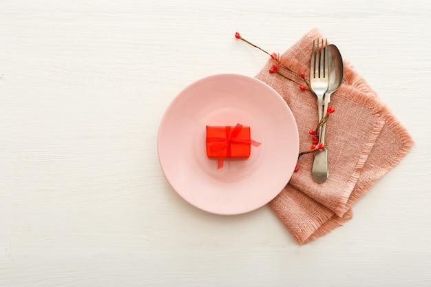 Сервировка стола на день святого валентина на ужин из белого деревянного стола в ресторане на день святого валентина