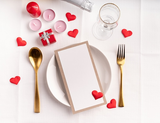 Valentines day table setting with menu, plate, bottle of champagne top view, mock up design