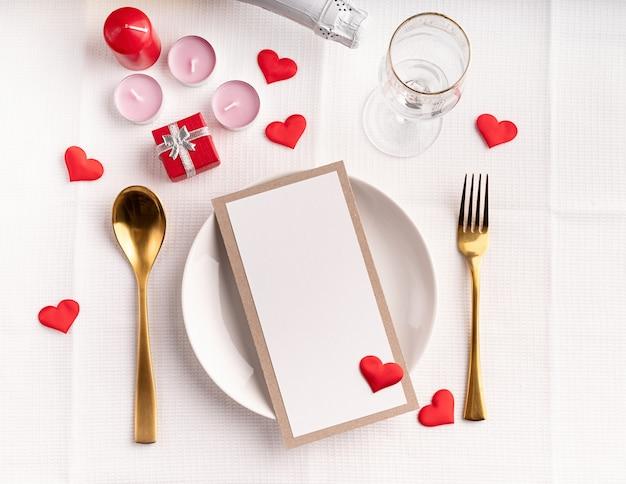 Сервировка стола на день святого валентина с меню, тарелка, бутылка шампанского, вид сверху, макет дизайна