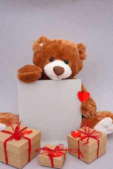 Valentines day teddy bear holding place for text, red heart and gift box. retro romantic style. creative greeting card.