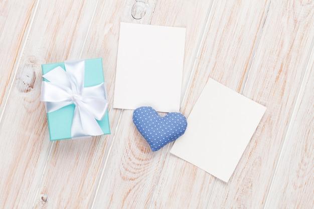 バレンタインデーのおもちゃの心、空白のフォトフレームと木製のテーブルの背景上のギフトボックス